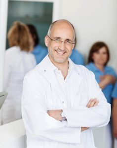 Portrait of male mid adult dentist smiling with assistants in background at clinic